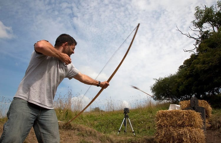 man practice shooting on haybales